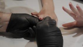 O homem profissional do manicuro fricciona seus pés com um pano anestésico filme