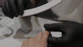 O homem profissional do manicuro lustra e alisa os pregos da menina com um arquivo de prego vídeos de arquivo