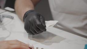 O homem profissional do manicuro retira ferramentas para o tratamento de mãos antes do procedimento vídeos de arquivo