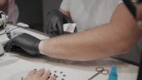 O homem profissional do manicuro retira ferramentas para o tratamento de mãos antes do procedimento video estoque