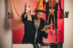 O homem pronuncia um período, lê um livro mágico Decoração de Dia das Bruxas e conceito assustador Música da noite 31 de outubro fotos de stock