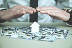 O homem protege a casa de papel com uns dólares Seguro da casa Foto de Stock Royalty Free