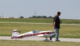 O homem puxa Airplane modelo vermelho Fotografia de Stock
