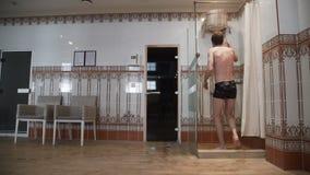 O homem puxa a corda e derrama a água fora da cubeta Chuveiro frio dentro após a sauna vídeos de arquivo