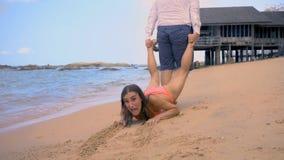 O homem puxa uma menina ao longo do litoral, a menina resiste e quer descansar mais, o conceito do fim do feriado fotos de stock royalty free