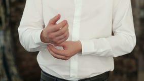 O homem que abotoa botões nas luvas de sua camisa Close-up filme