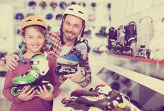 O homem que ajuda seu filho a tentar sobre patina Imagem de Stock Royalty Free