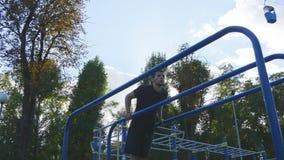 O homem que atlético fazer empurra levanta em barras paralelas na terra de esportes no parque da cidade Formação muscular nova fo imagens de stock