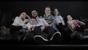 O homem que coloca no sofá com as crianças no cinema vídeos de arquivo