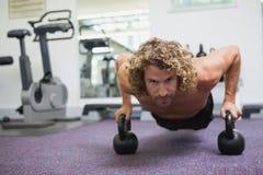 O homem que considerável fazer empurra levanta com os sinos da chaleira no gym Fotografia de Stock