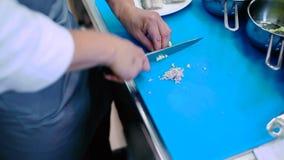 O homem que corta um alho em umas partes pequenas na placa filme