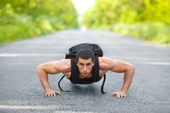O homem que da aptidão exercitar empurra levanta, exterior Cruz-treinamento masculino muscular no parque da cidade Imagens de Stock Royalty Free