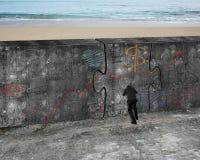 O homem que empurra a porta enorme do enigma do negócio rabisca o muro de cimento Foto de Stock