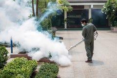 O homem que enevoa-se para eliminar o mosquito Fotografia de Stock
