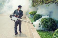 O homem que enevoa-se para eliminar o mosquito Fotos de Stock Royalty Free