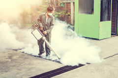 O homem que enevoa-se para eliminar o mosquito para impede a febre de dengue da propagação Fotos de Stock Royalty Free