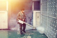 O homem que enevoa-se para eliminar o mosquito para impede a febre de dengue da propagação Imagem de Stock