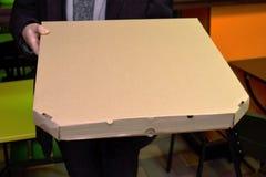 O homem que entrega a pizza está guardando uma grande caixa com um tamanho da pizza de 50 centímetros ou de 20 polegadas foto de stock royalty free