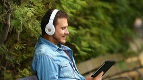 O homem que escuta refrigera para fora a música em um parque filme