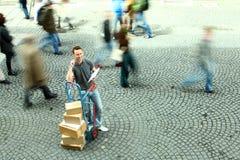O homem que está com Dolly Of Boxes While Crowd anda perto Imagem de Stock Royalty Free