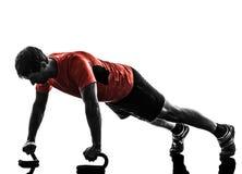 O homem que exercita o exercício da aptidão empurra levanta a silhueta Fotografia de Stock Royalty Free