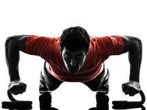 O homem que exercita o exercício da aptidão empurra levanta a silhueta Fotografia de Stock