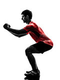 O homem que exercita o exercício da aptidão investe contra a silhueta de agachamento Fotografia de Stock