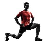O homem que exercita o exercício da aptidão investe contra a silhueta de agachamento Imagens de Stock Royalty Free