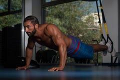 O homem que exercitar empurra levanta com as correias da aptidão de Trx Imagem de Stock Royalty Free