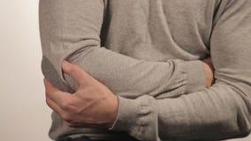 O homem que faz massagens o cotovelo devido à dor aguda em um fundo branco video estoque