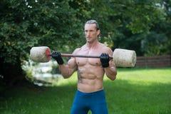 O homem que faz o exercício para o bíceps fora malha Fotografia de Stock Royalty Free