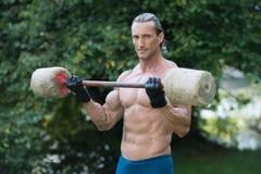 O homem que faz o exercício para o bíceps fora malha Imagem de Stock