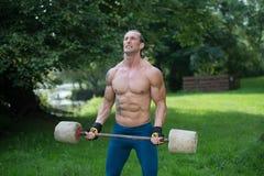 O homem que faz o exercício para o bíceps fora malha Foto de Stock
