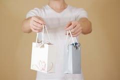 O homem que guarda o saco de papel do presente da placa dois disponivéis com corações zomba acima Imagem de Stock