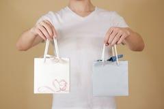 O homem que guarda o saco de papel do presente da placa dois disponivéis com corações zomba acima Fotografia de Stock Royalty Free