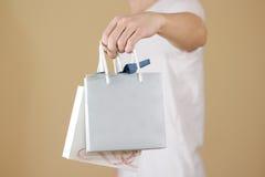 O homem que guarda o saco de papel do presente da placa dois disponivéis com corações zomba acima Fotos de Stock Royalty Free