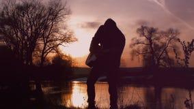O homem que joga a guitarra na silhueta do por do sol video estoque