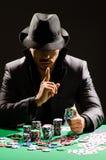 O homem que joga no casino escuro fotos de stock