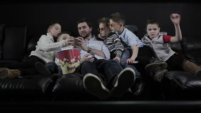 O homem que joga no smartphone com as crianças no cinema vídeos de arquivo