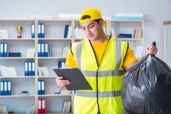 O homem que limpa o escritório e que guarda o saco de lixo foto de stock