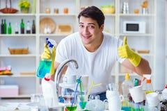 O homem que mostra os polegares que lavam acima pratos imagens de stock