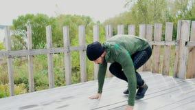 O homem que novo forte fazer empurra levanta verão masculino do ar livre do treinamento do exercício do desportista do atleta que filme