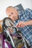 O homem que olha seriamente em bicicletas roda foto de stock royalty free