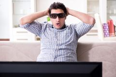 O homem que olha a tevê 3d em casa Fotografia de Stock