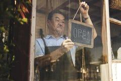 O homem que pendura um aberto assina dentro um florista fotografia de stock royalty free