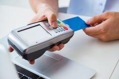 O homem que processa a transação do cartão de crédito com terminal da posição imagens de stock royalty free