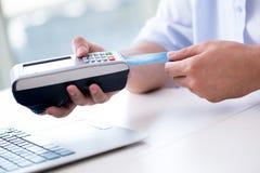 O homem que processa a transação do cartão de crédito com terminal da posição foto de stock royalty free