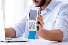 O homem que processa a transação do cartão de crédito com terminal da posição fotos de stock