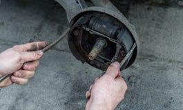 O homem que repara cilindros de freio para o carro e as verificações as pastilhas dos freios usando duas chaves de fenda imagens de stock royalty free