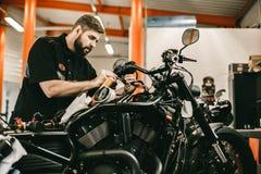 O homem que repara a eletrônica ostenta a bicicleta preta Imagem de Stock Royalty Free